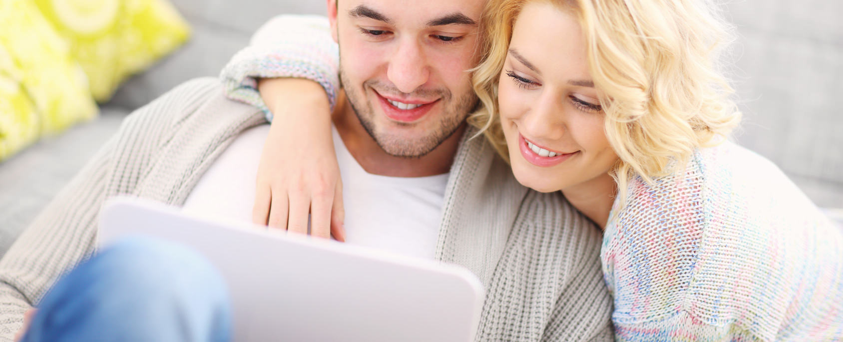 Adult couple using laptop at home